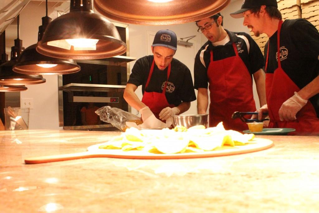 Line cooks Zach Ohmie, Victor Romero, and Nate Hodson prepare a nacho dish on Beau Jo's.