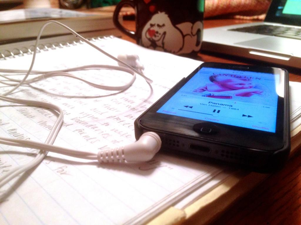 phone with a playlist lying on some notes