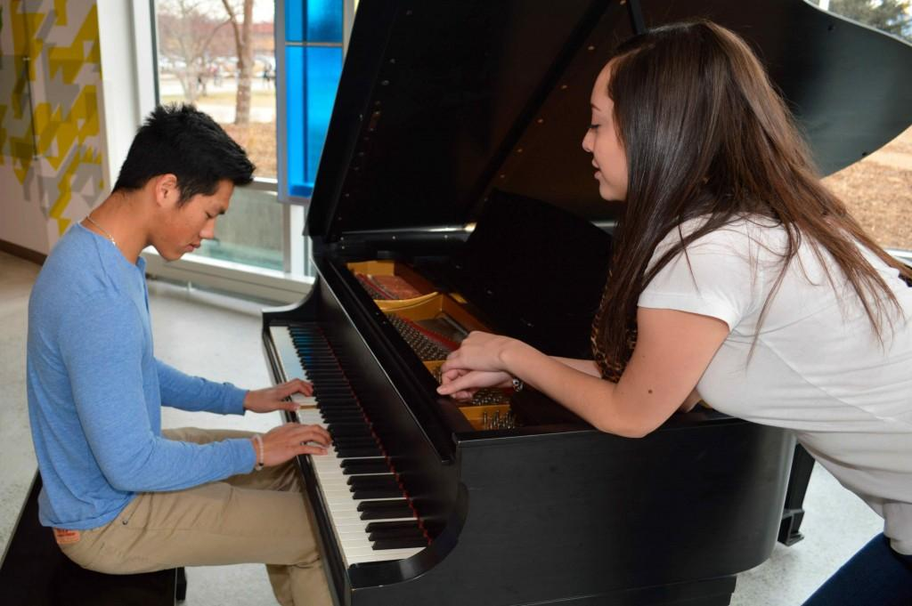 Boy plays the piano for a girl.