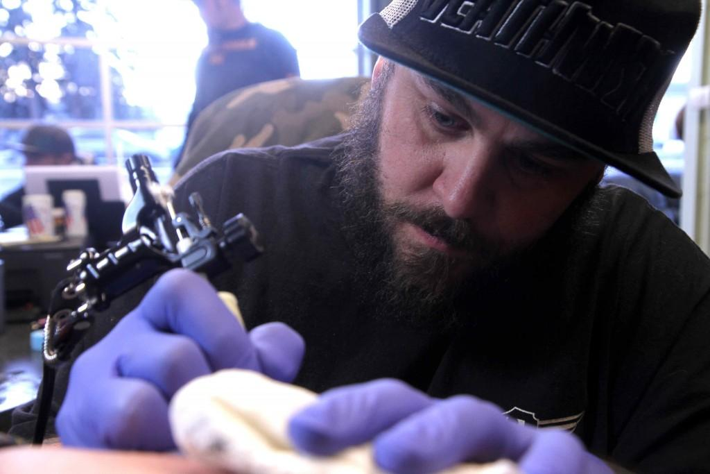 Rob Nicholl carefully tattoos an atom symbol on Vera Bendoni's side at Covenant Tattoo shop.