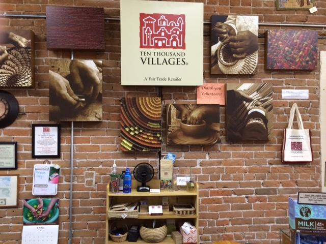 wall of Ten Thousand Villages with store sign and photography of people crafting their products