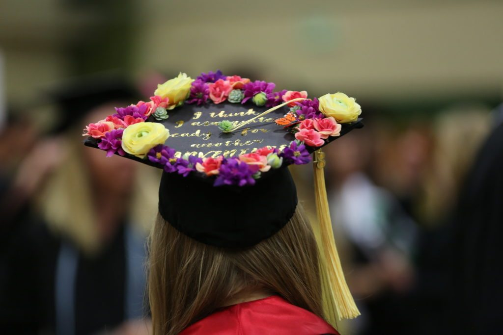 A graduate shows off her decorated cap.