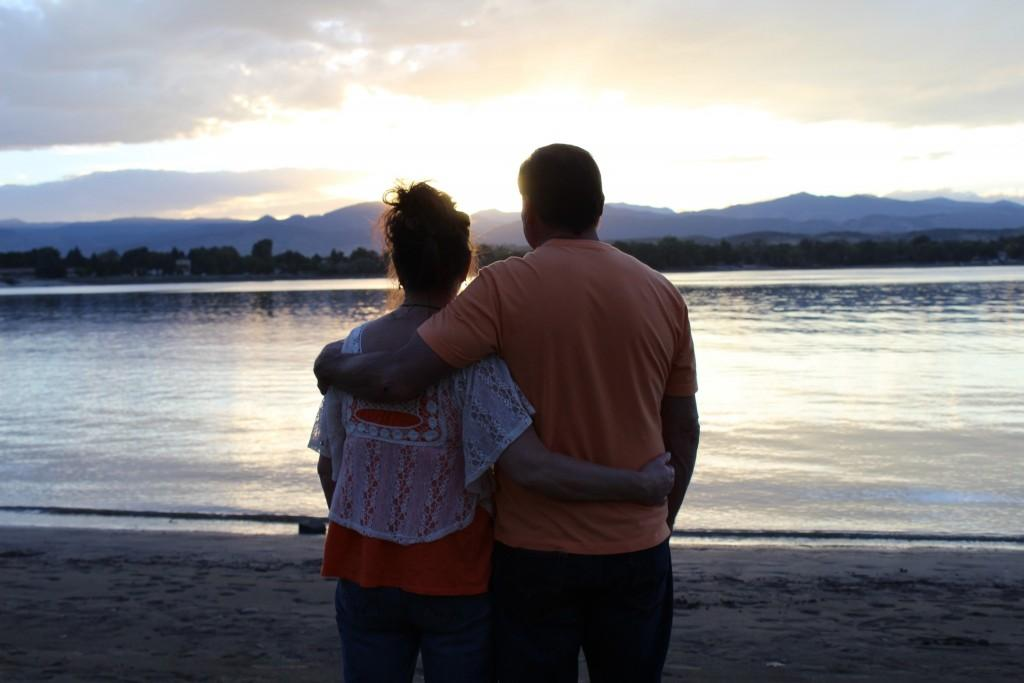 two people with arms around each other watching the sunset