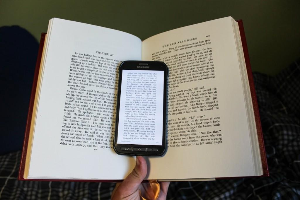 phone with text opened on it lying in the middle of an open book