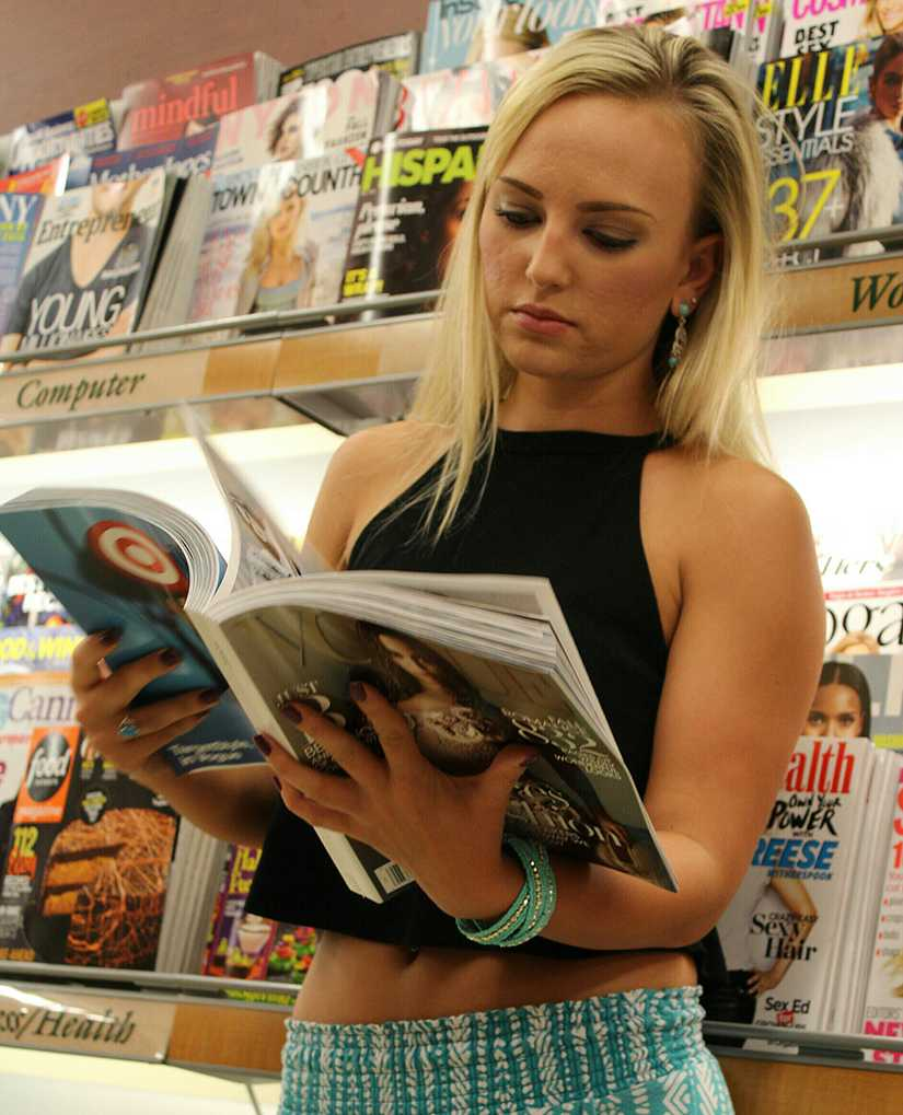 blonde woman browsing a fashion magazine in front of a magazine stand