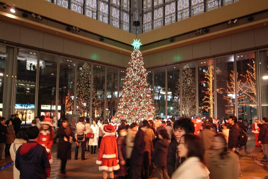 Christmas tree lit in a busy plaza