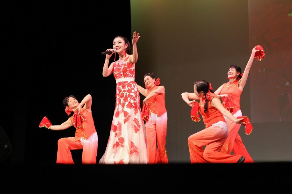 Chinese performers on stage dressed in red