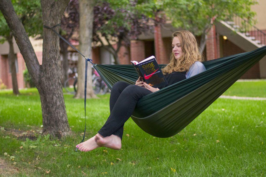 "A girl sits in a green hammock reading the book ""Shoe Dog."""