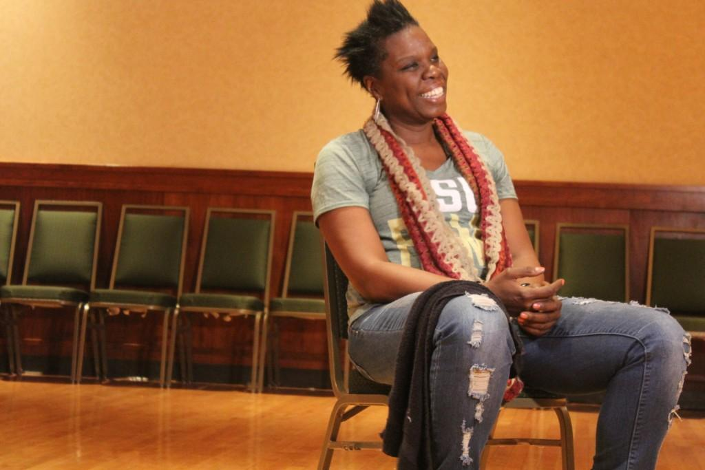 Leslie Jones sitting and smiling in casualwear