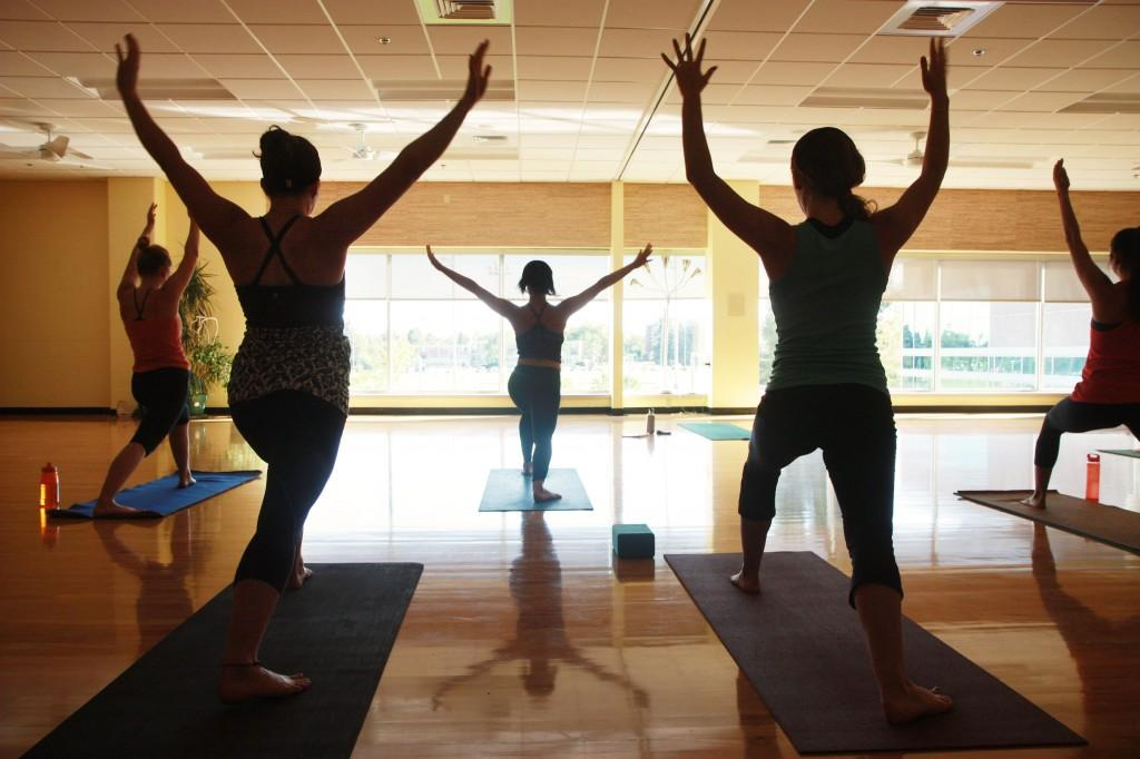 people in arms raised yoga pose silhouetted by window light