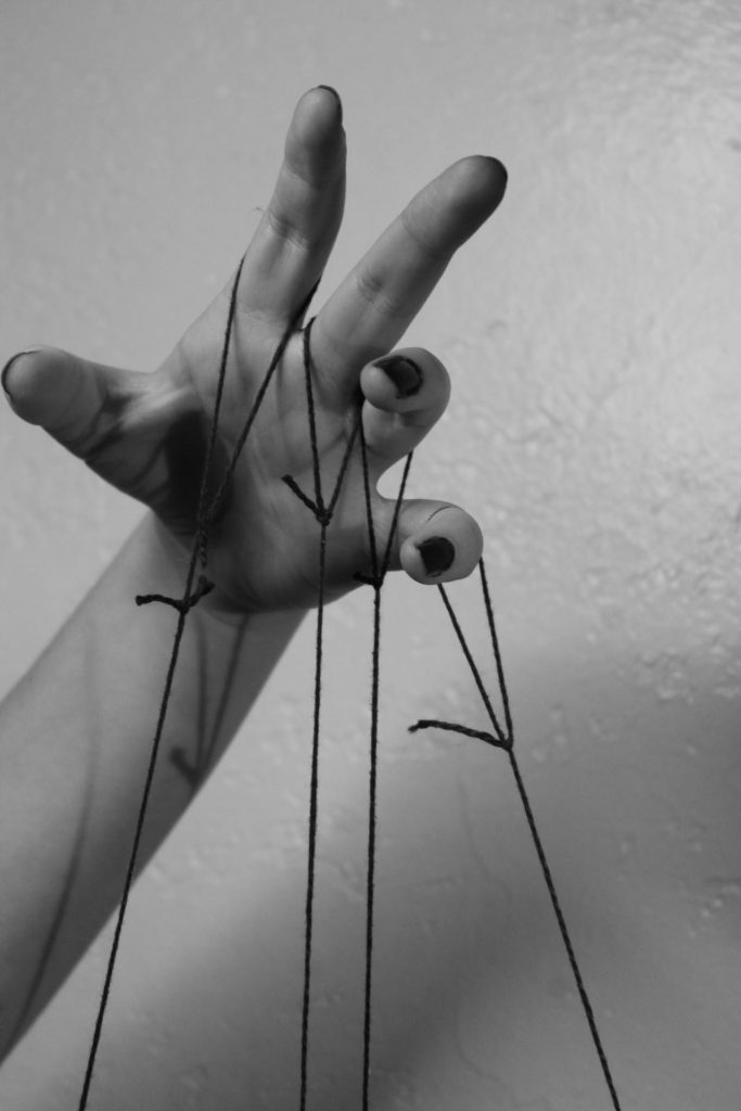 hand holding puppet strings
