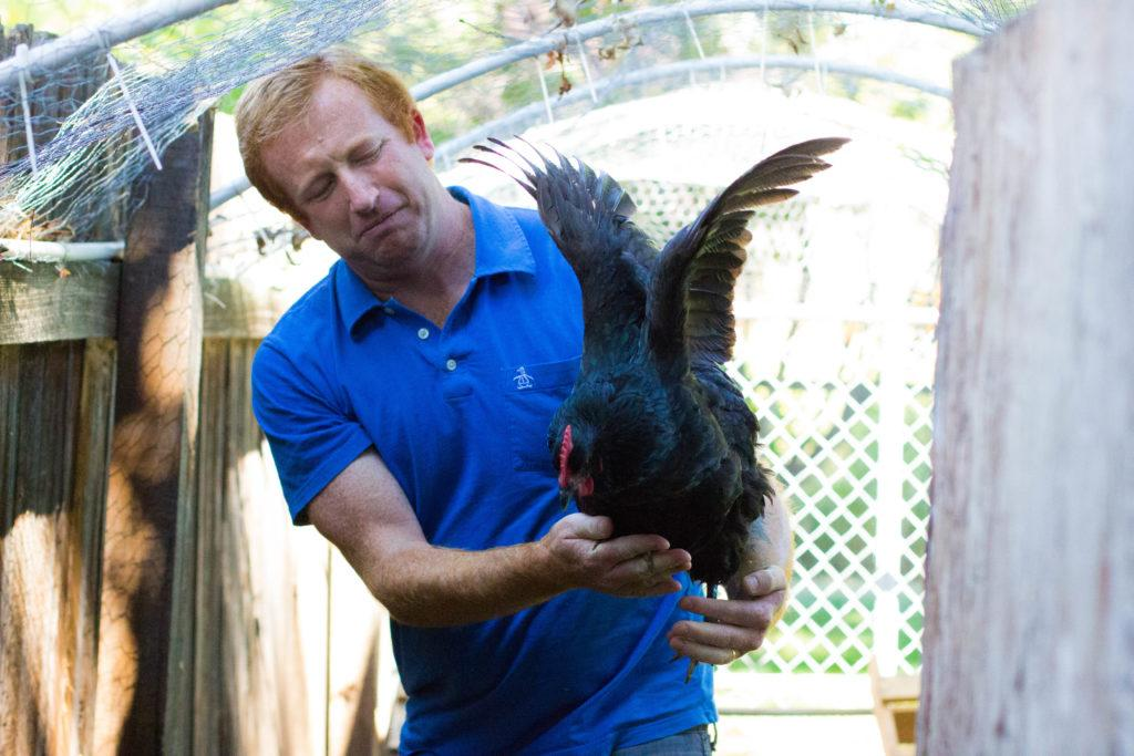 man holding a chicken while it flaps it wings