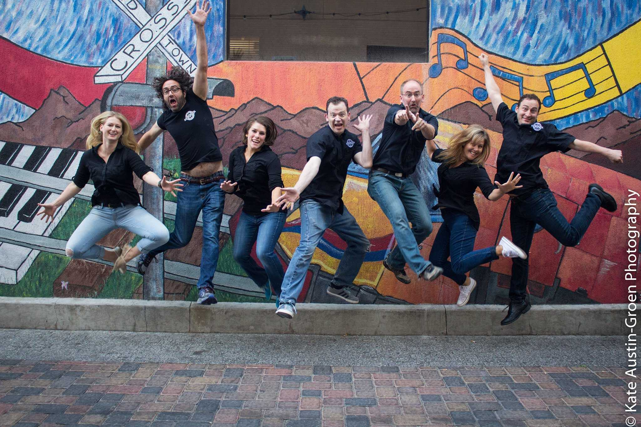 Members of the Comedy Brewers jumping up in smiles in front of Old Town mural