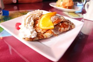 crepe with whipped cream and orange slice on top