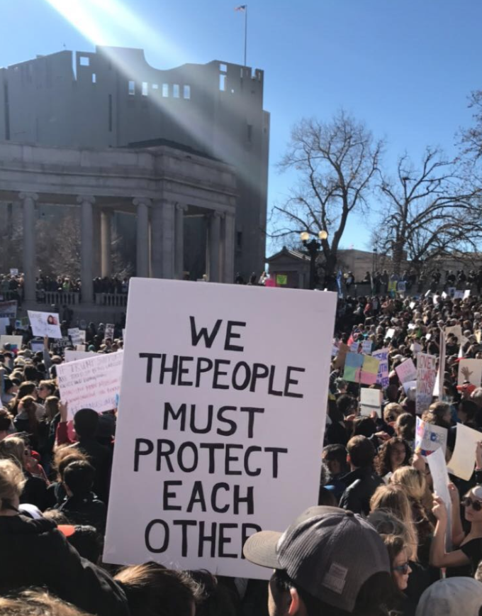 """sign at a protest that reads """"We the people must protect each other"""""""