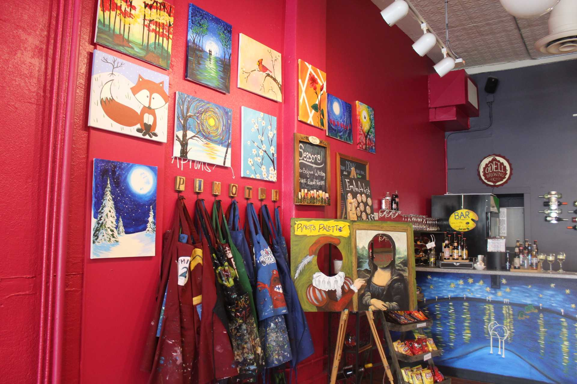painting smocks hung on wall with paintings at Pinot's Palette