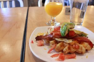 The Blue Sky Breakfast waffle piled high with eggs, bacon, tomatoes and avocado.