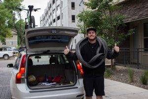 Jimmy Yoder posing by his car with his mountain bike tires on his neck.