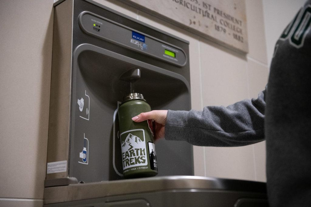 student refilling water bottle at refill station