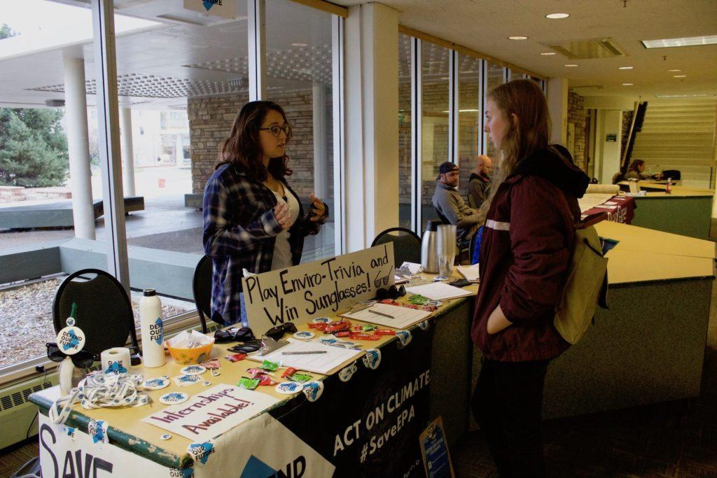 Student talks to a Defend Our Future volunteer at the organization's table set in the Lory Student Center at CSU. Photo credit: Abby Flitton