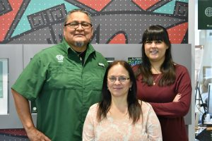 Director of NACC Ty Smith (left), Assistant Director Tiffani Kelly (right), and Administrative Assistant Teresa Rice (center) stand in front of the cultural center in the LSC. Photo credit: Kelly Peterson