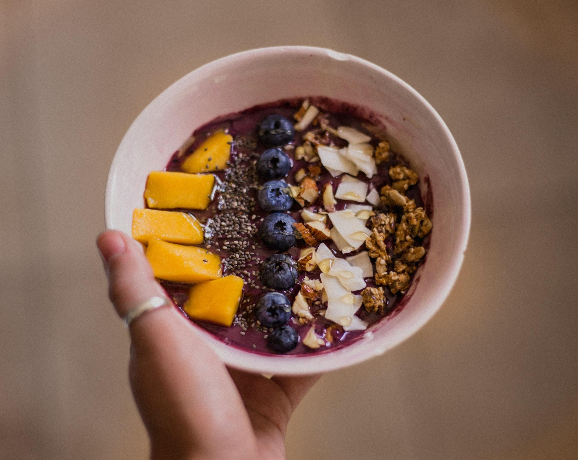 upper view of an acai bowl smoothie topped with blueberries and granola