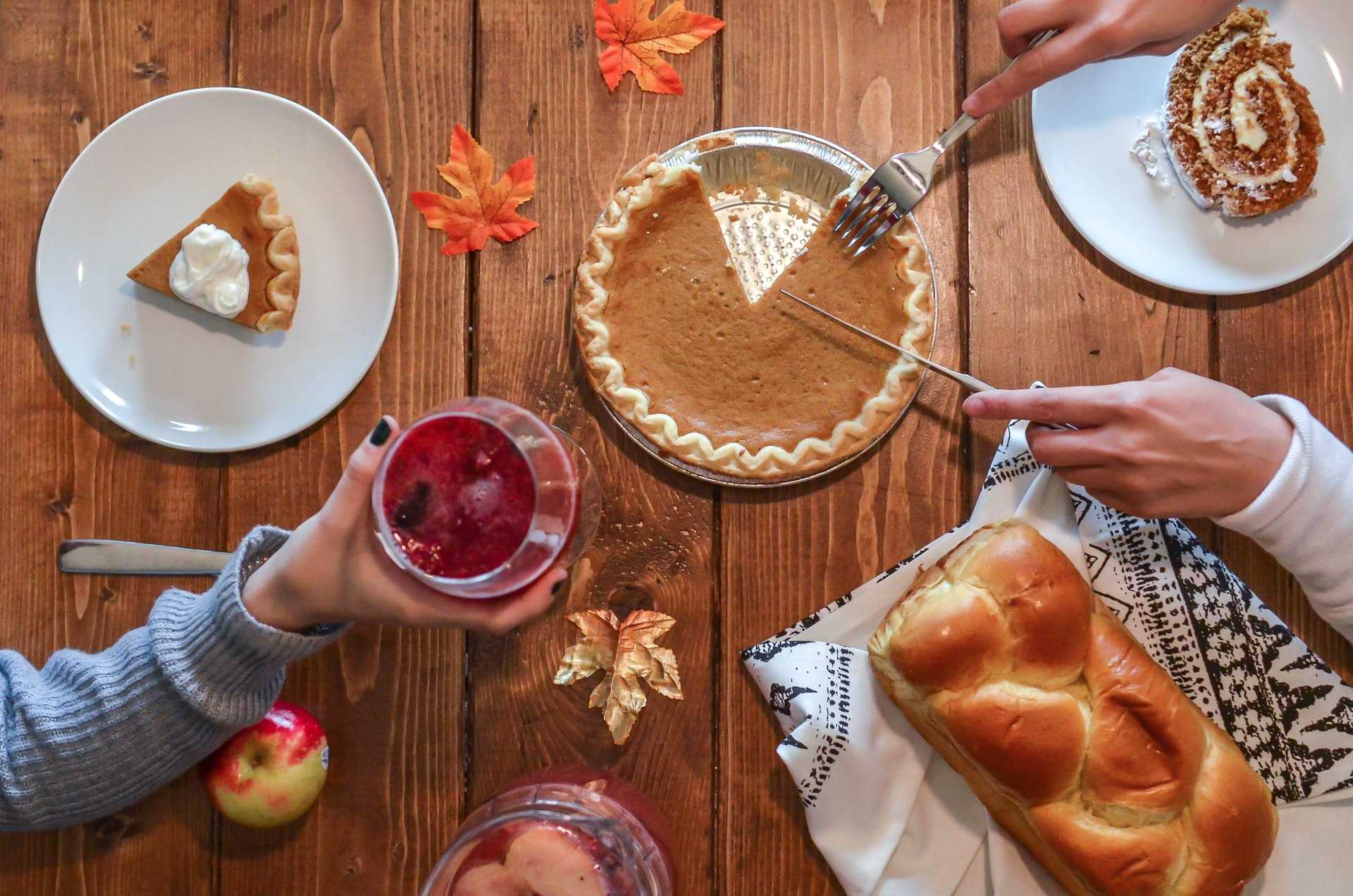 top view of table with pumpkin pie and fall leaves on it