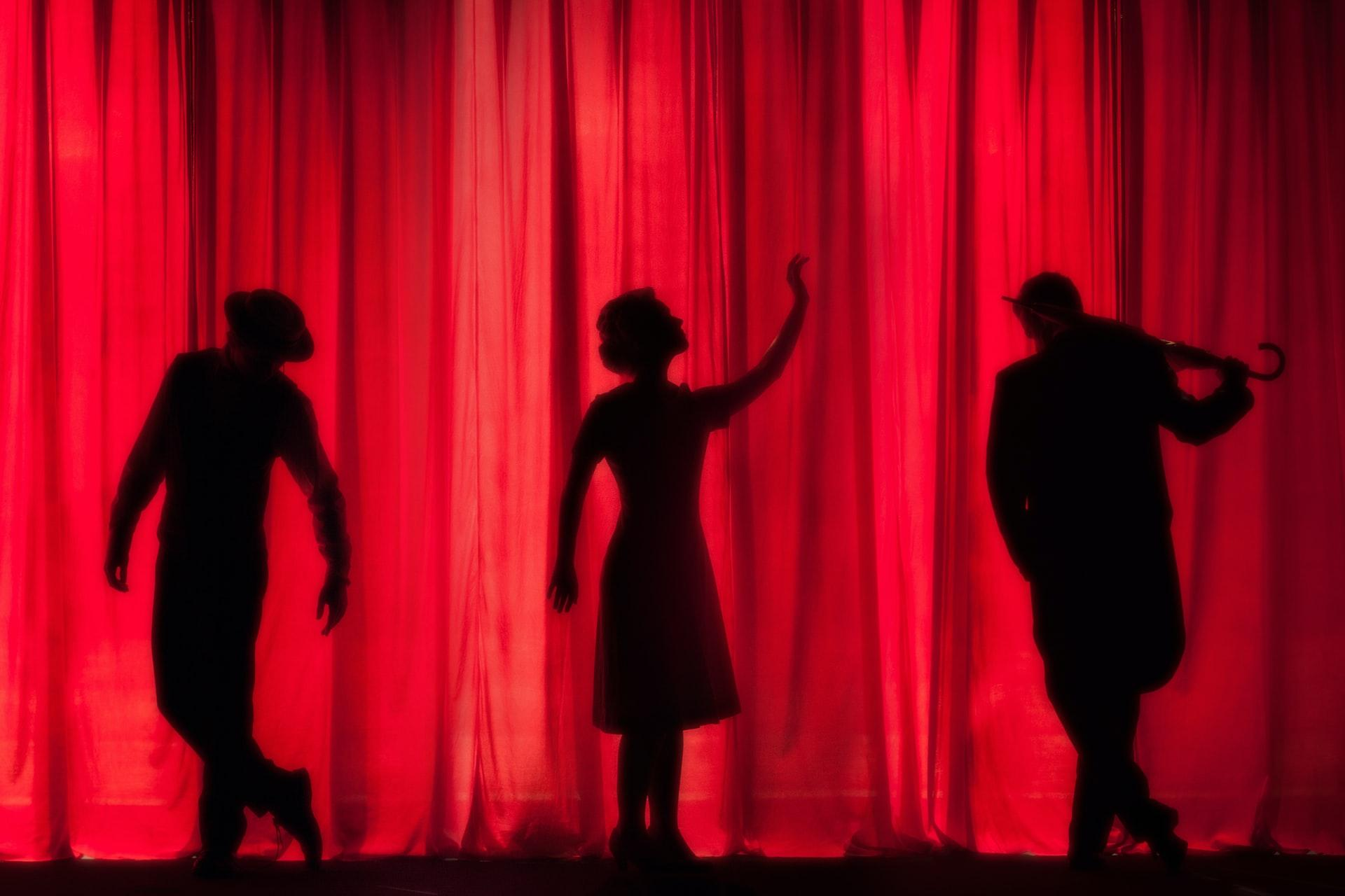 sihouette of a woman dancing with two male silhouettes on either side of her. they are behind a red, backlit stage curtain