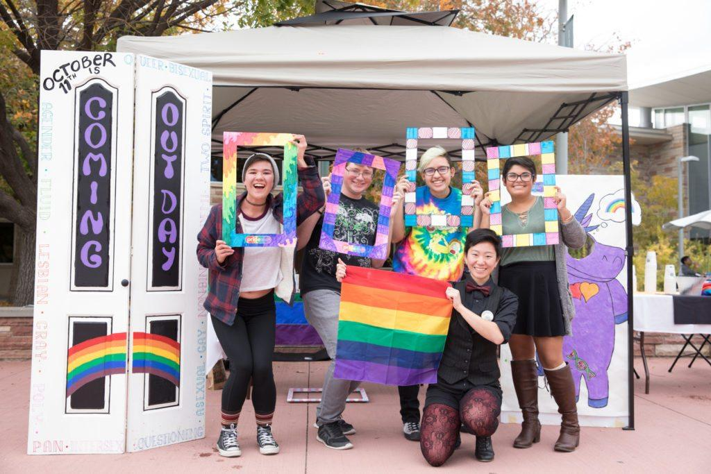 white students posing for group photo with rainbow items