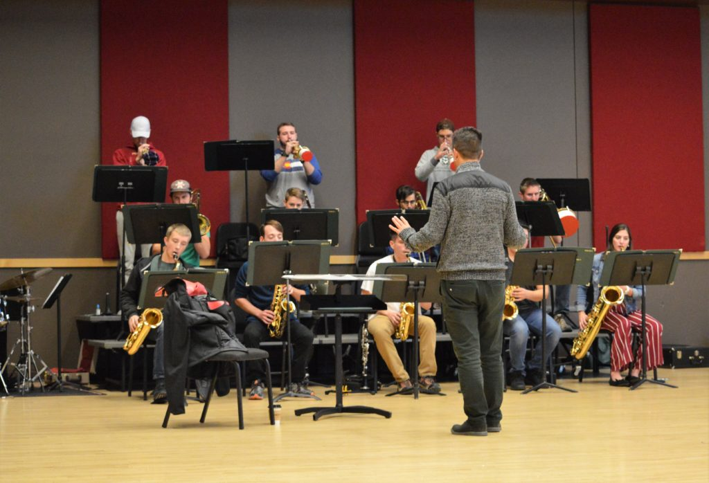 man conducts student performers