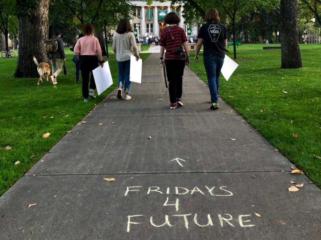 """four students holding protest signs walking toward the CSU admin building. Sidewalk chalk on ground reads """"Fridays 4 Future"""""""