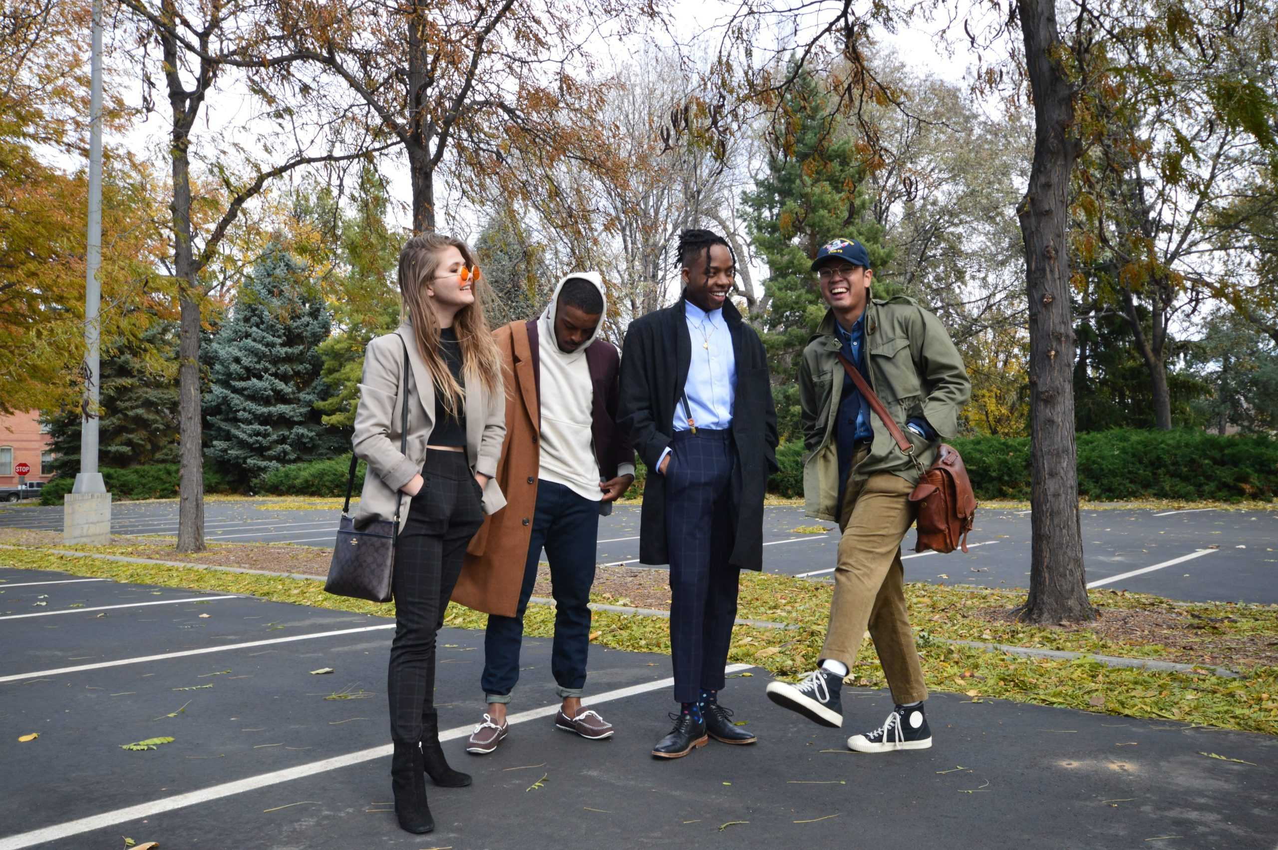 Four people, one white woman, two black men, and one Filipino man, stand in a parking lot dressed in fashionable Ivy style