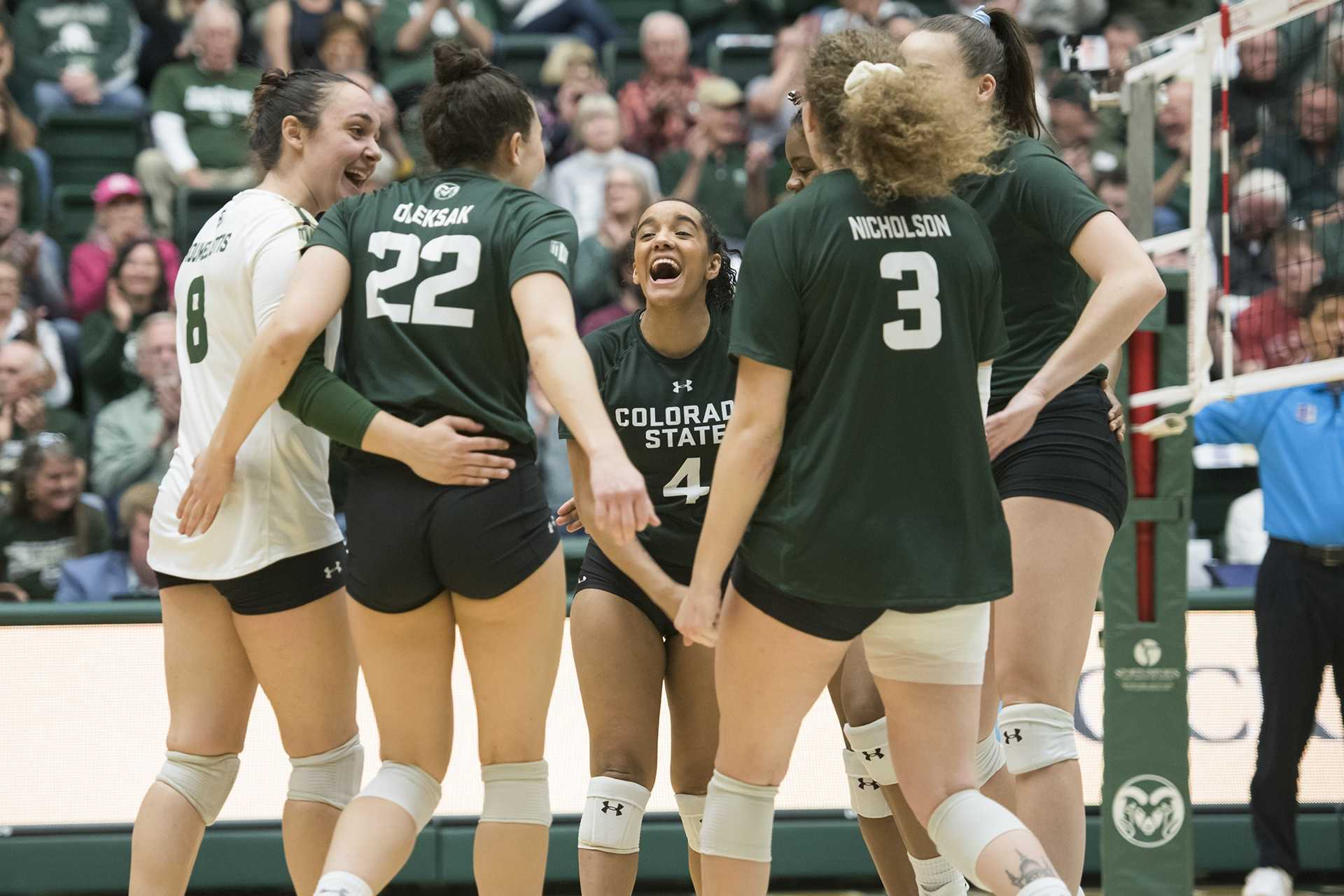 Freshman Brooke Hudson celebrates a point in the huddle with her volleyball teammates in the second match.
