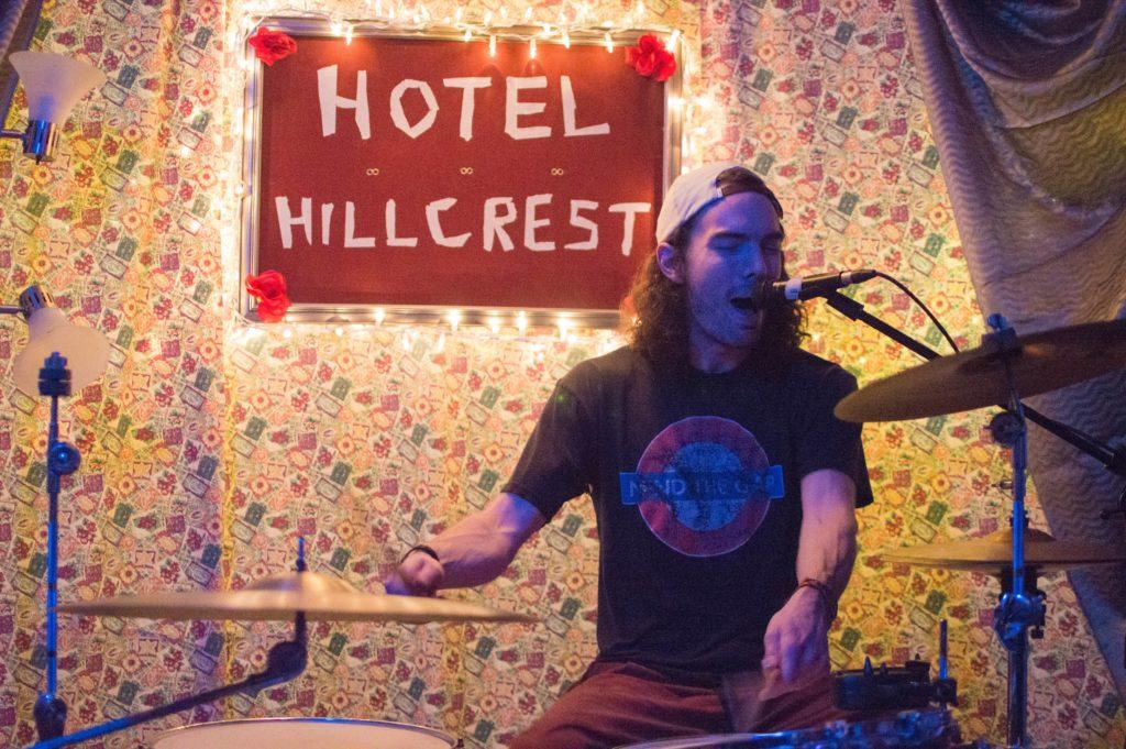 DIY venues in Fort Collins: Drummer playing music in front of Hotel Hillcrest sign