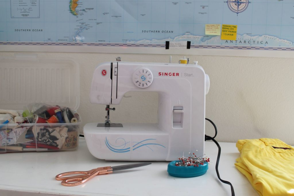 A white sewing machine on a desk workspace meant for clothing alterations