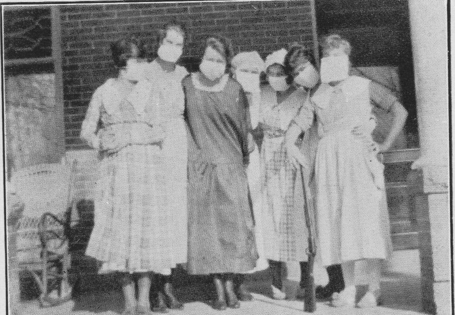 historical photo of women wearing masks standing arms around each other