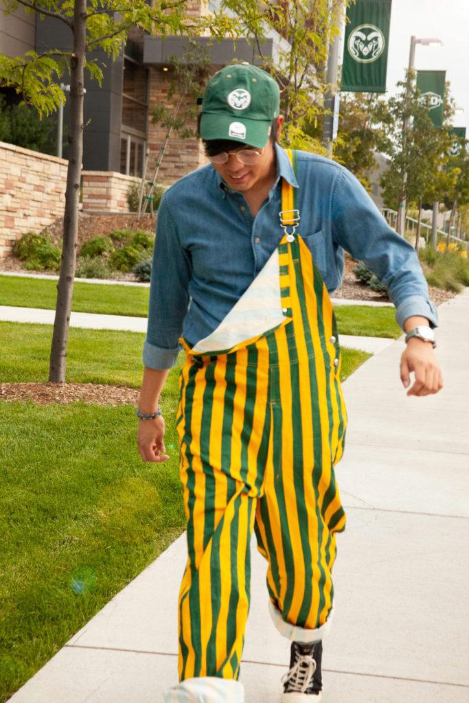 man poses in green and yellow striped overalls