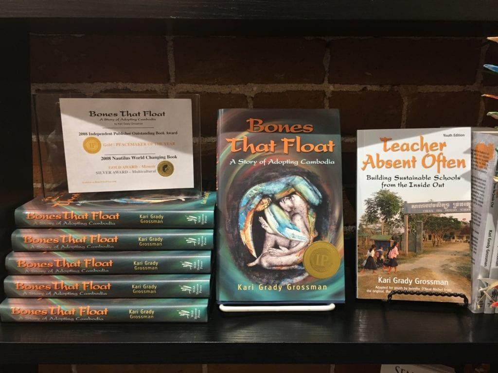 """Books """"Bones That Float"""" and the youth edition """"Teacher Absent Often"""" sit on a display shelf"""