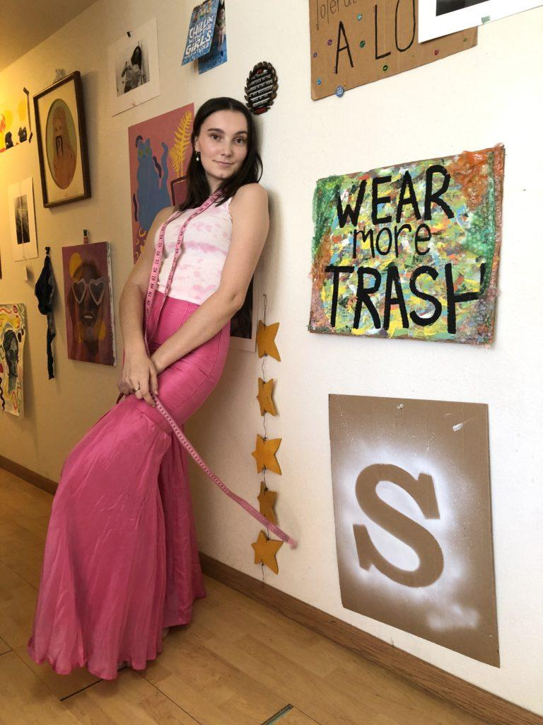 """(From Fast Fashion to Sustainable Styles)Sara VanHatten leans against her wall next to a sign reading """"Wear more TRASH"""""""