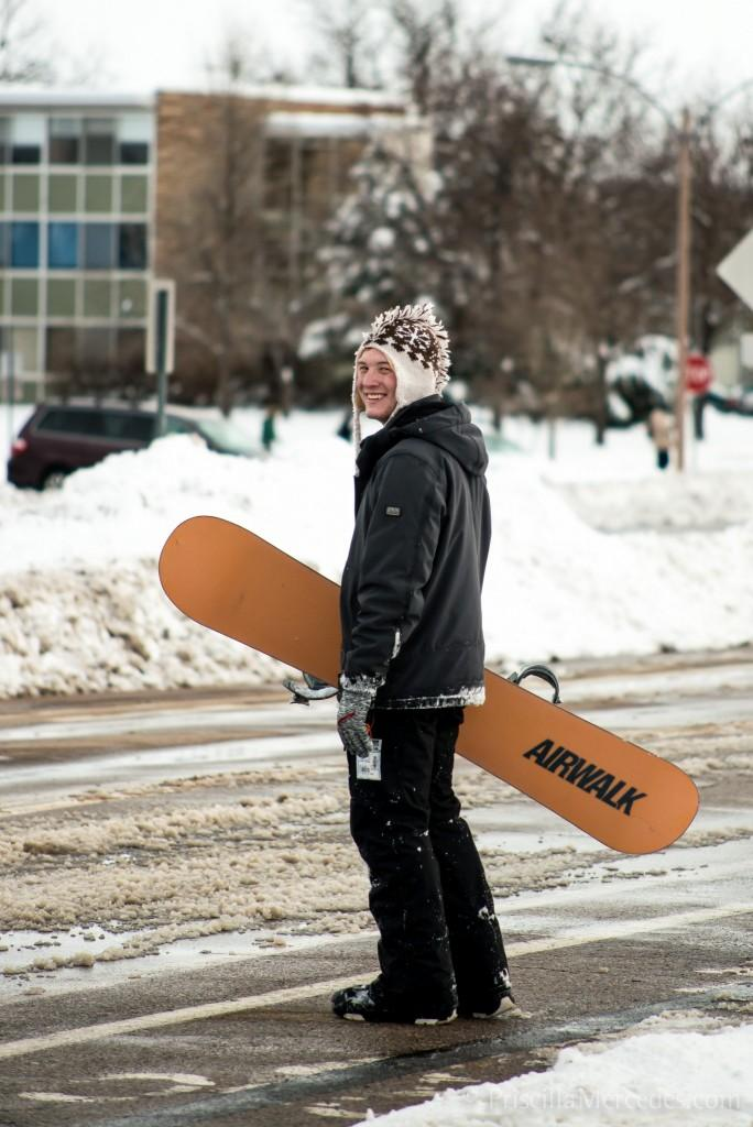 student in a hat with snowboard in a snowy street