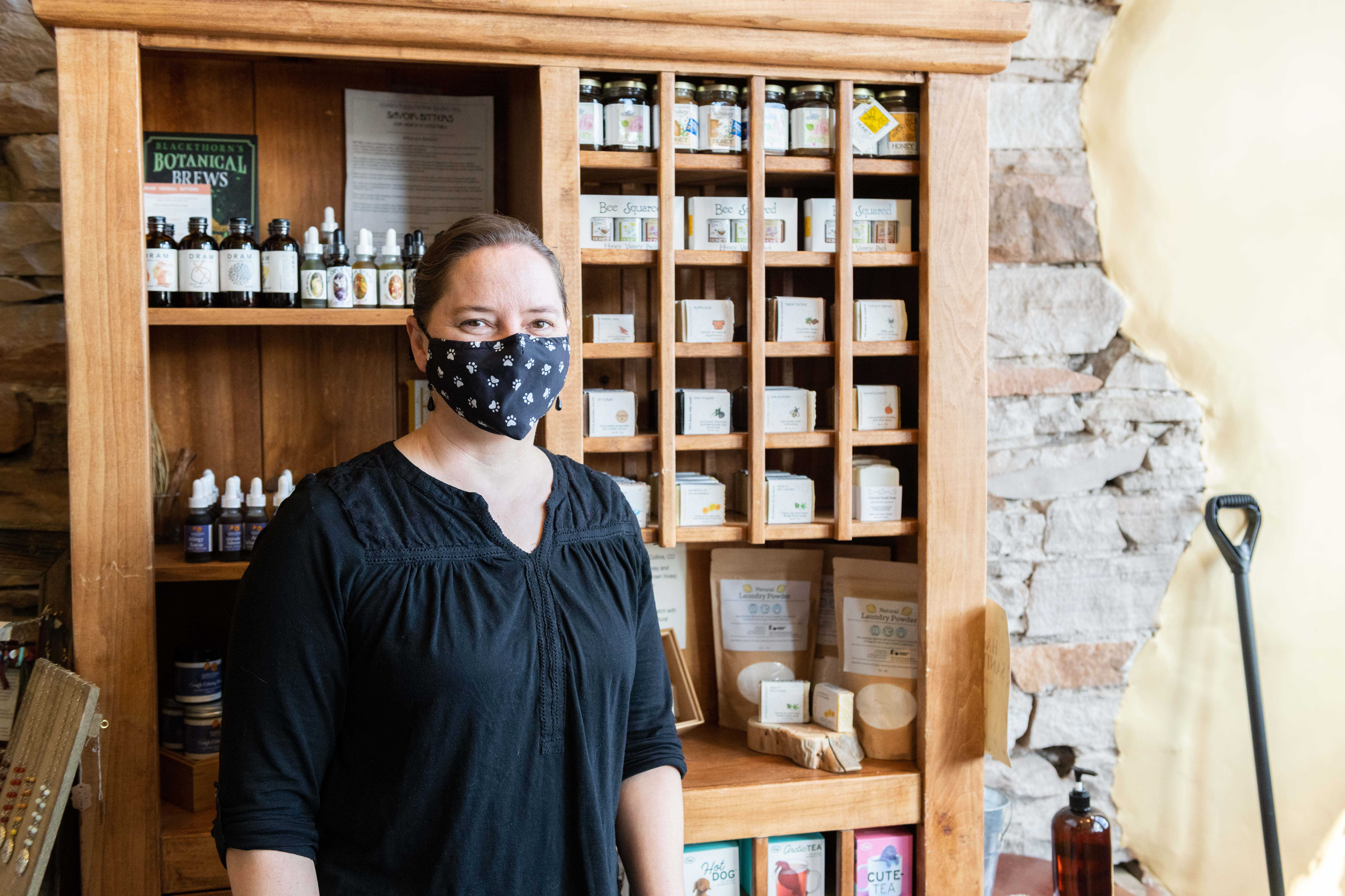 Marisa May, Sunlit Mountain founder, stands next to a shelf of her products