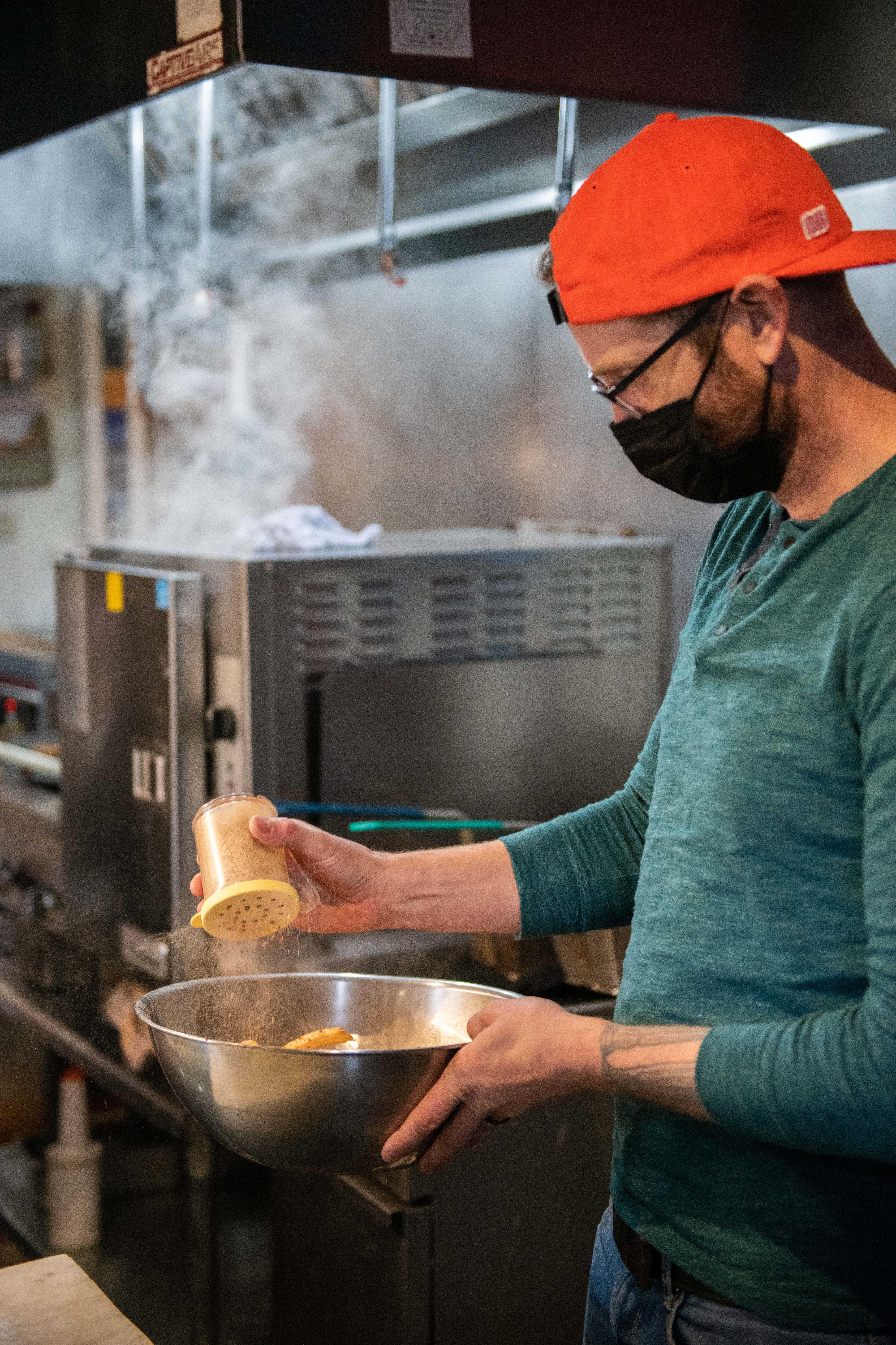 A Rama Mama chef seasons a bowl of fries.