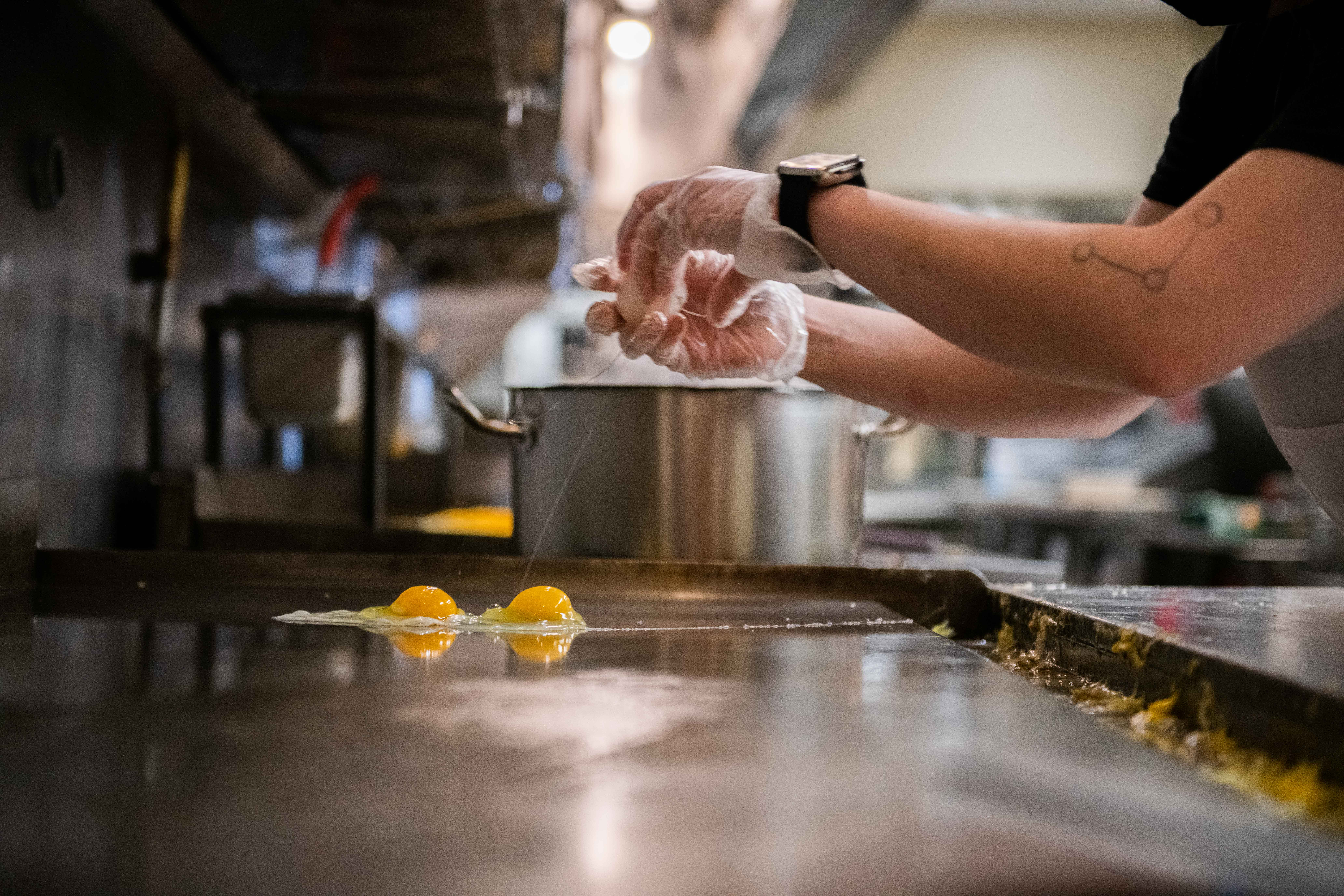 worker frying eggs on a skillet at Silver Grill