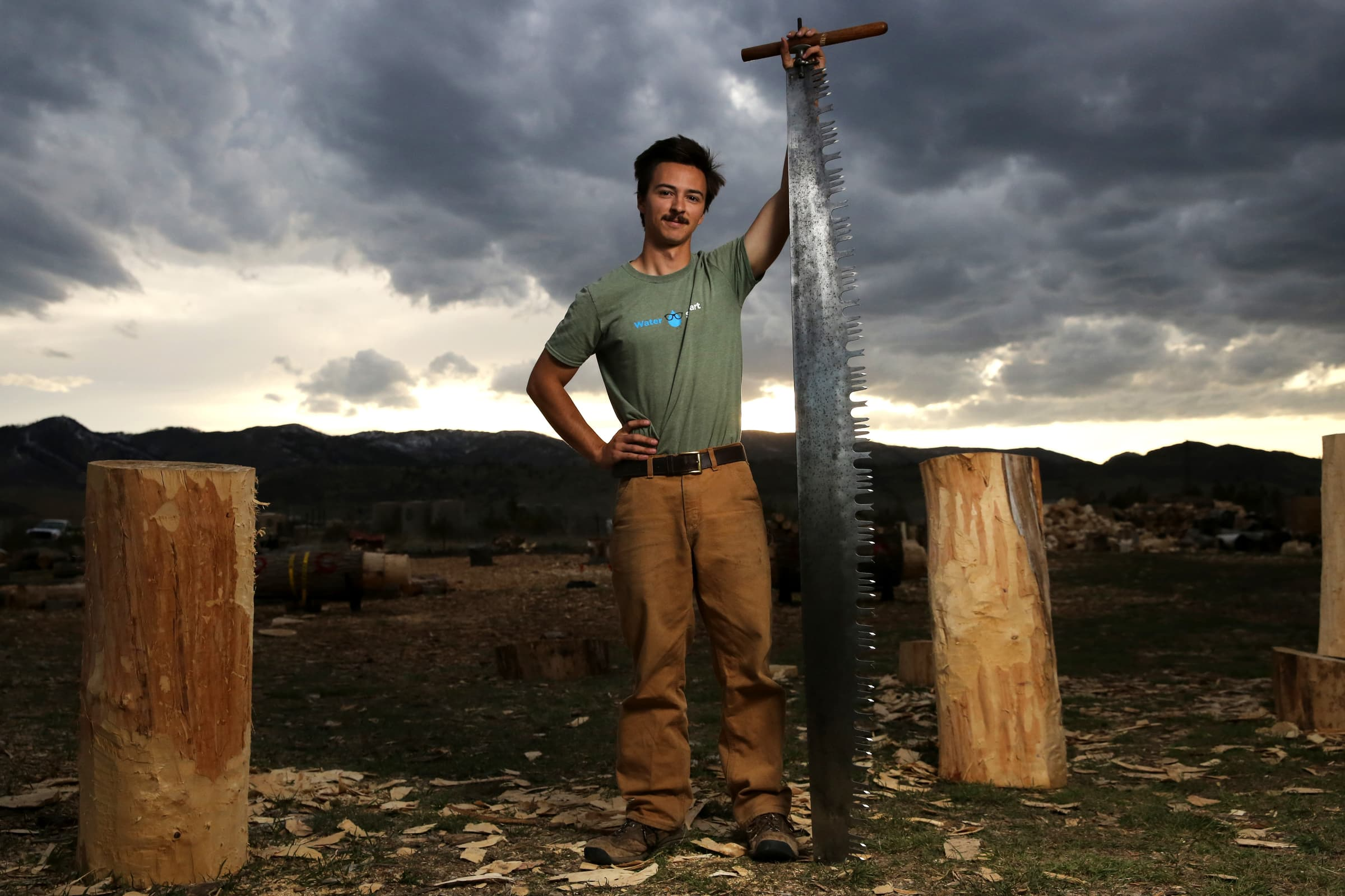 a man stands with a tall saw
