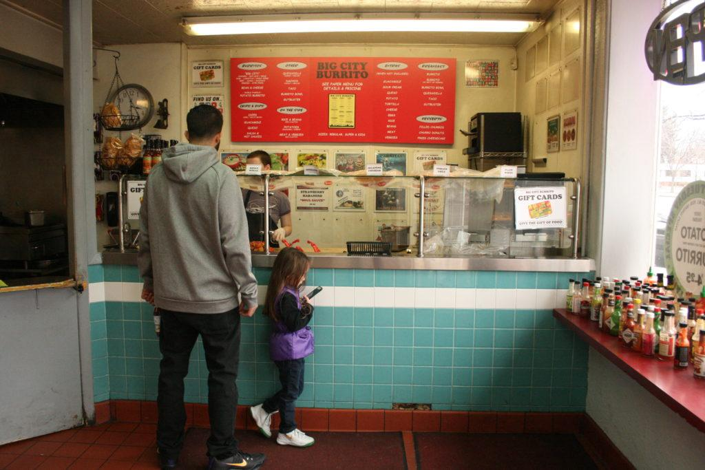 adult man and little girl order from the counter of Big City Burrito