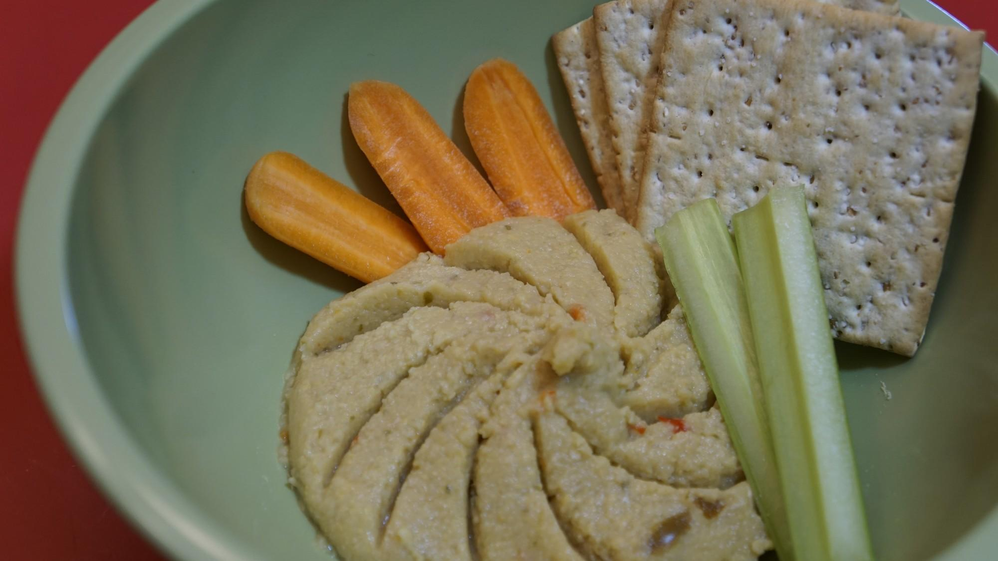 close up of hummus platter with carrots and crackers and celery